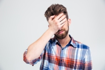 Portrait of upset man covering his face with hand isolated on a